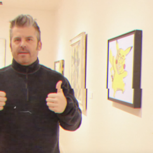 A man stands in front of a gallery wall with thumbs up