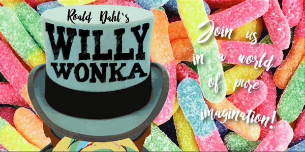 A top hat that reads Willy Wonka, sitting among gummy worms