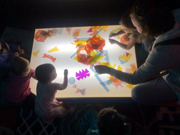 Children playing with the light board during Spill Squish Crunch