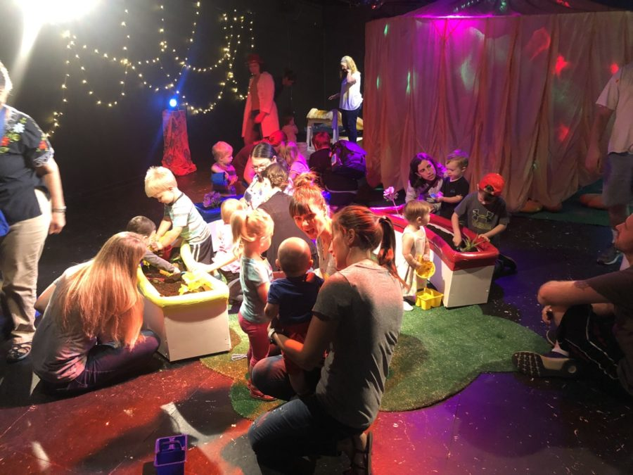 Children and adults play in a sandbox of soil and flowers. A large tent is lit with bright colors.
