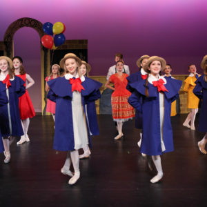 "Dancers are posed on stage as the girls in ""Madeline"" with capes and hats on stage"