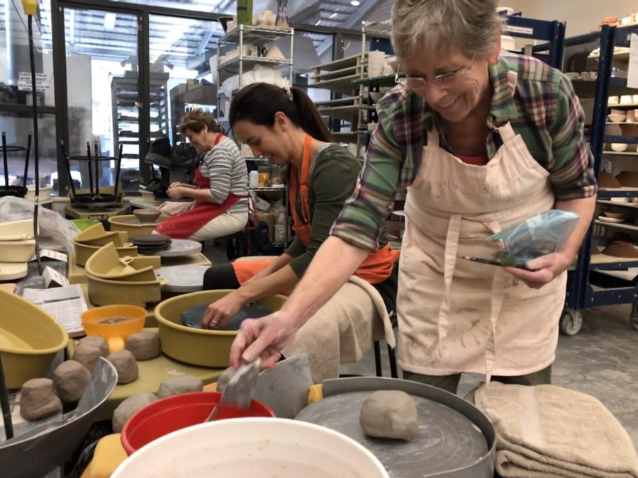 Three ceramic artists throw on the pottery wheel