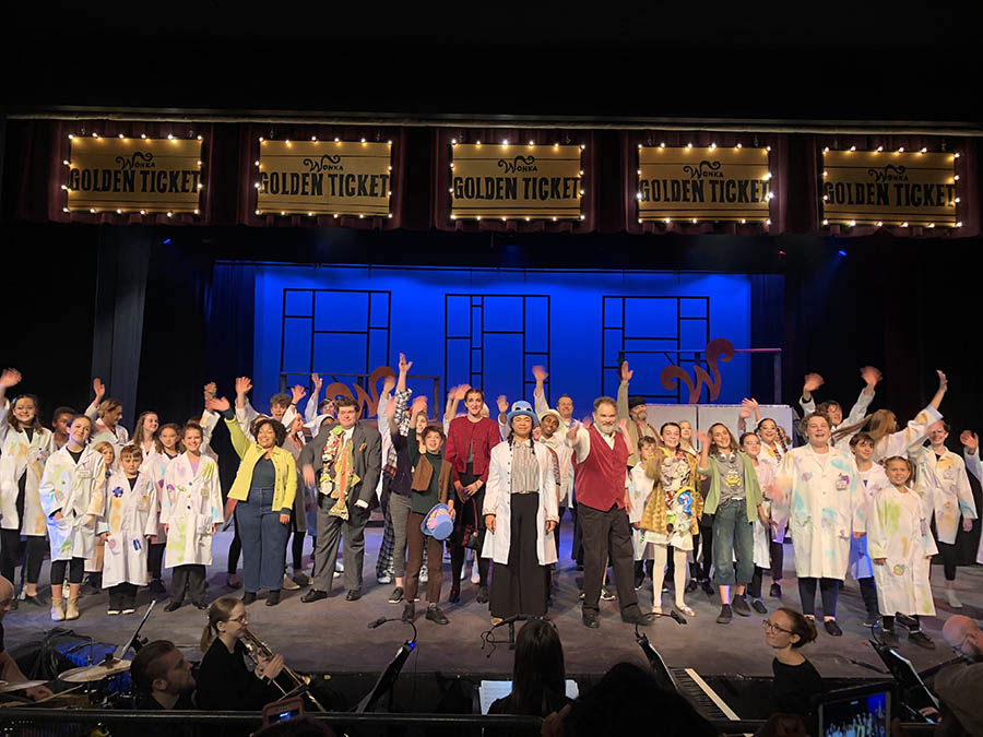 A stage full of cast members from Willy Wonka wave to the audience during curtain call