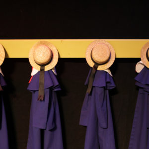 A line of neatly hung up Madeline hat and capes