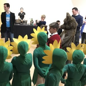 A woman speaks on a microphone in front of a group of kids dressed in sunflower costumes and adults in business attire