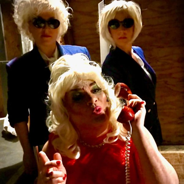 A man in a blonde wig answers a phone while two women in sunglasses pose behind him