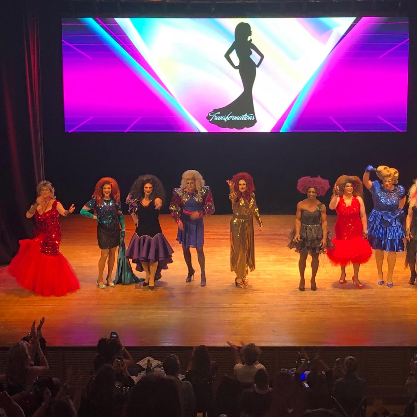 A group of drag queens pose on stage