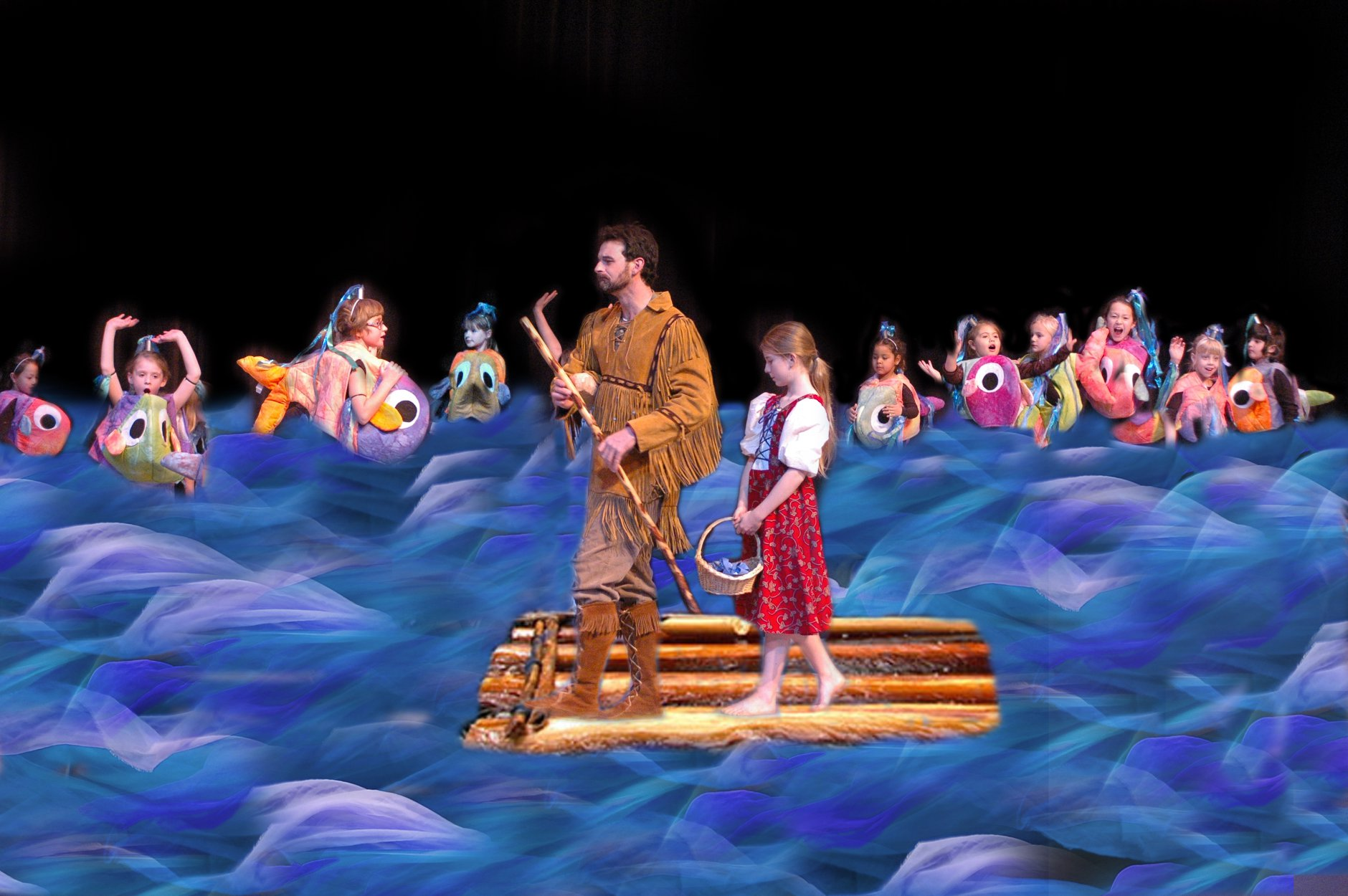 A young girl rides a raft with a man paddling through a school of tiny dancers dressed as fish.