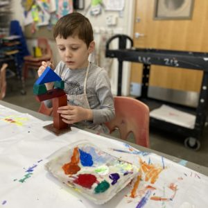 A boy at a table paints a geomteric sculpture.