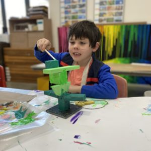 A boy at a table paints a small geometric sculpture.