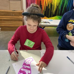 A girl colors pink stripes on a piece of paper featuring geometric design.