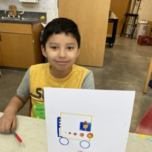 A child displays a geomtric drawing of a vehicle.