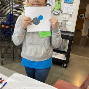 A young person displays a piece a paper featuring a geometric design.
