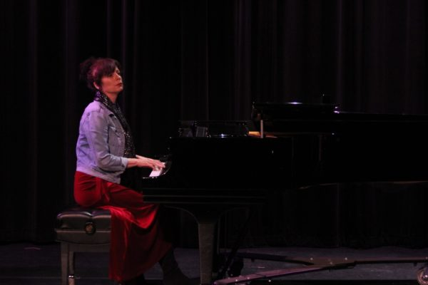 A woman plays the piano on stage.