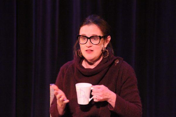 A women speaks on stage as she hold a coffee cup.