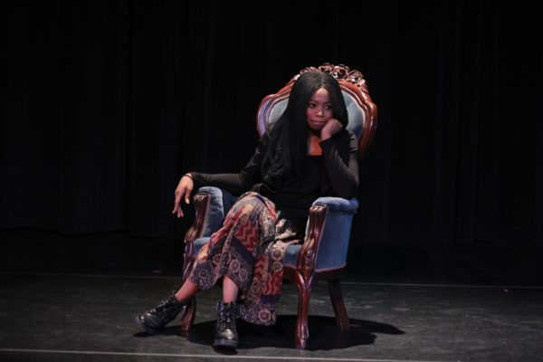 A woman sitting on stage in a velvet chair leans her chin into her hand.