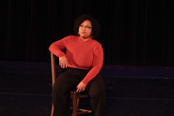 A woman sits on a chair on stage.
