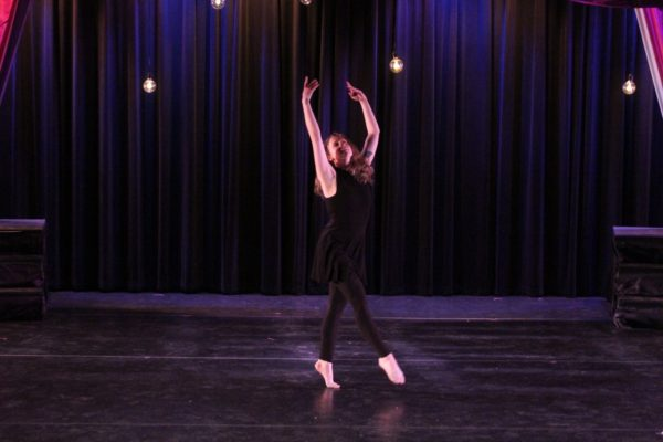 A woman dances alone on stage.