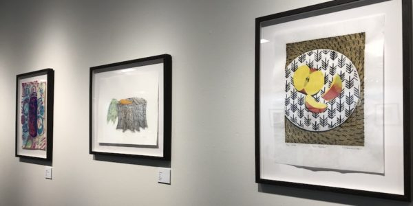 prints of food art hung on a gallery wall