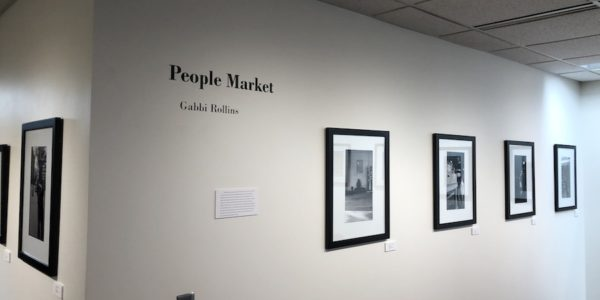 Black and white photographs of people on a gallery wall