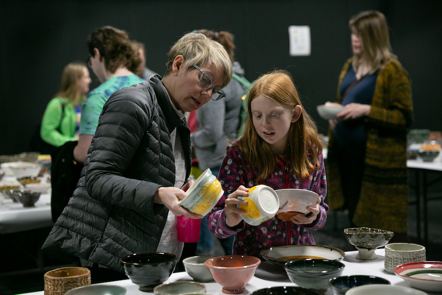 A woman and a girl look at ceramic bowls for sale