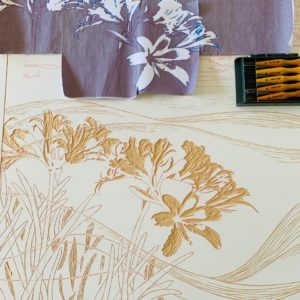 A woodcut lays on a table with wood-cutting tools resting on top.