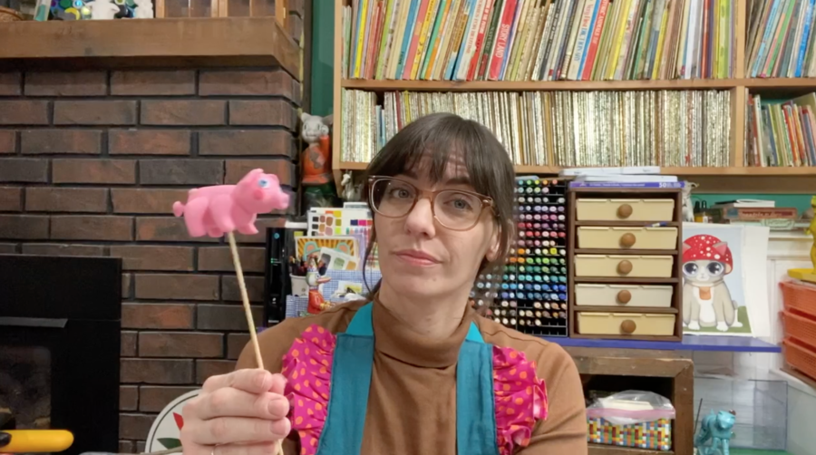 A woman holds a small plastic pig on a stick.