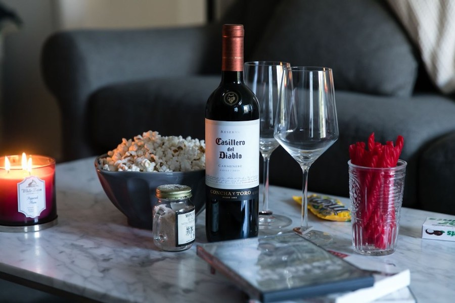 A table holding a candle, popcorn, licorice, M&Ms, a bottle of wine and wine glasses.