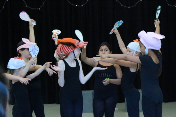 Young dancers wearing hats hold paddles and point at a center dancer.