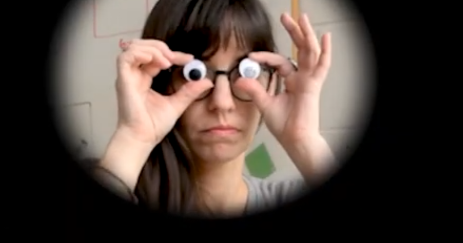 A woman holds googly eyes in front of her own eyes.