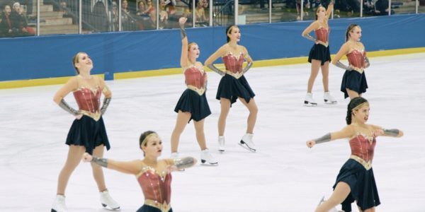Seven skaters dressed as Wonder Woman stretching on an ice rink.