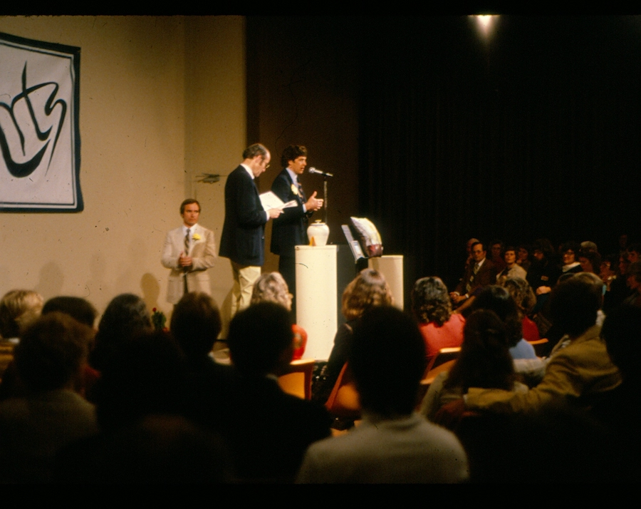 Two men at a podium auction off an urn in front of an audience.