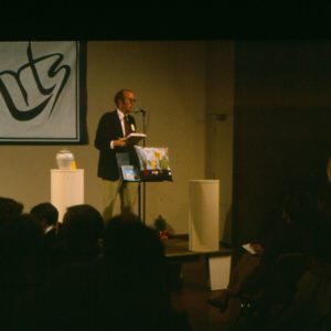 A man speaks into a microphone in front of an audience.