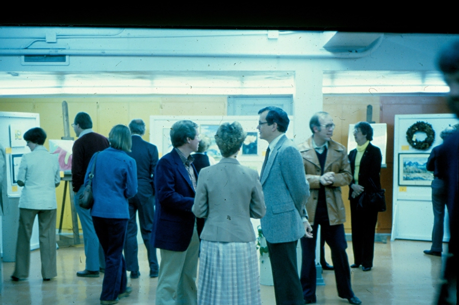 Vintage photo of a dozen people browsing auction pieces in a gallery.