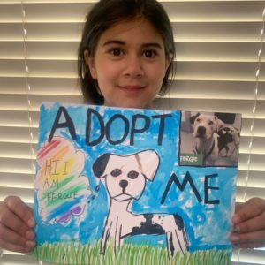 A girl holds up her pet adoption poster.