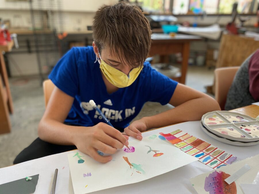 Young person paints on paper.