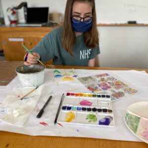 Young person works on flower painting.