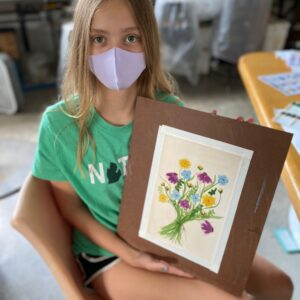 Young person holds up painting of flowers.