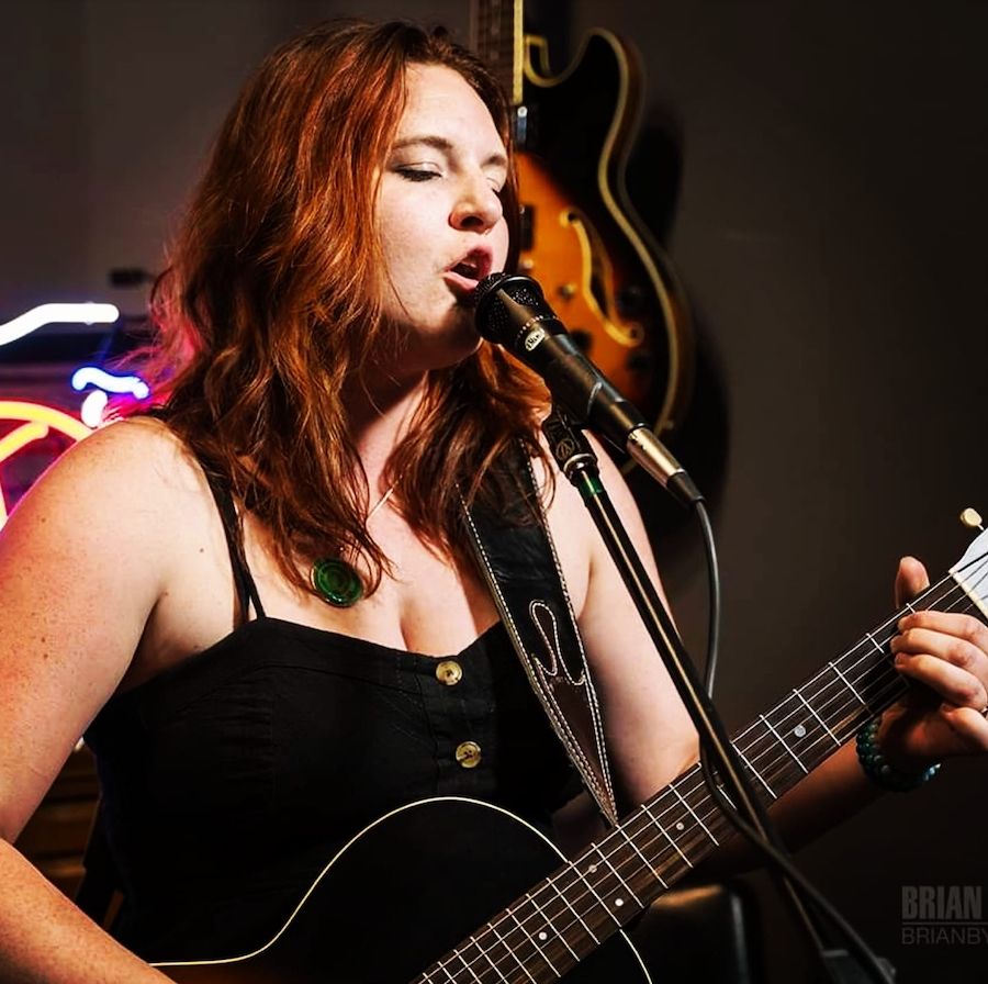 A woman plays guitar in front of a microphone