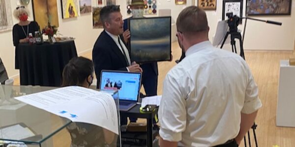 Behind the scene photos of man on camera during art auction.