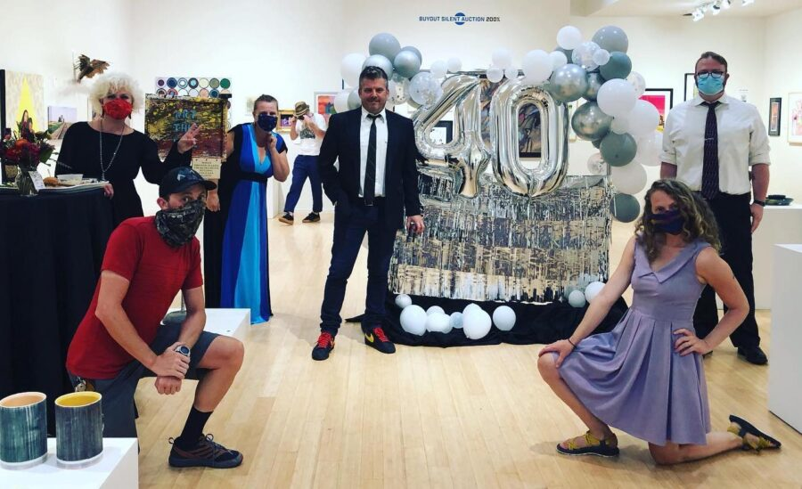 People pose in gallery with balloons.