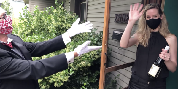 A man wearing a tuxedo presents a woman with a bottle of wine on her doorstep.