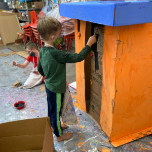 Children paint and construct box buildings.