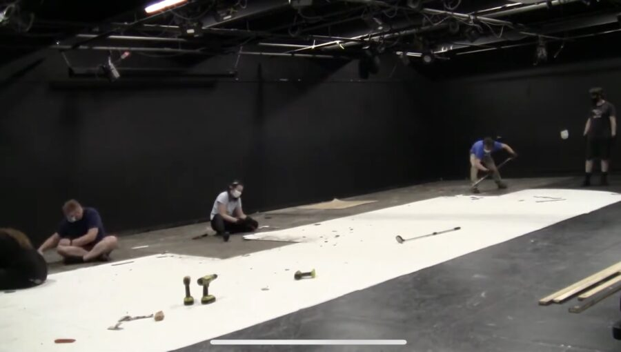 People installing flooring in theater.