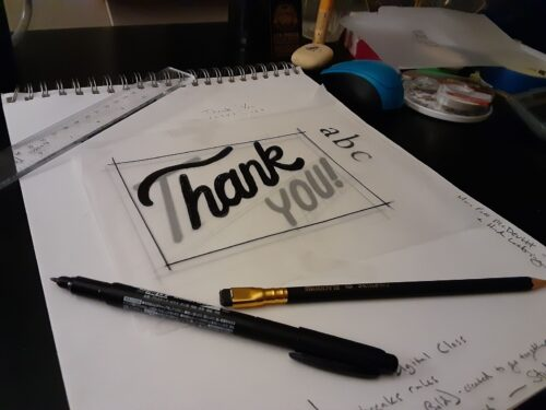 "Ink lettering that says ""thank you."""