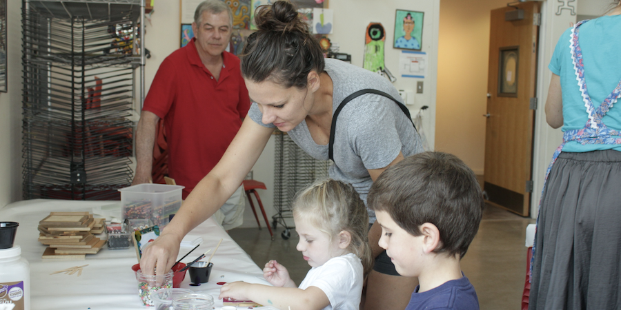 An adult helps a child in family arts class.