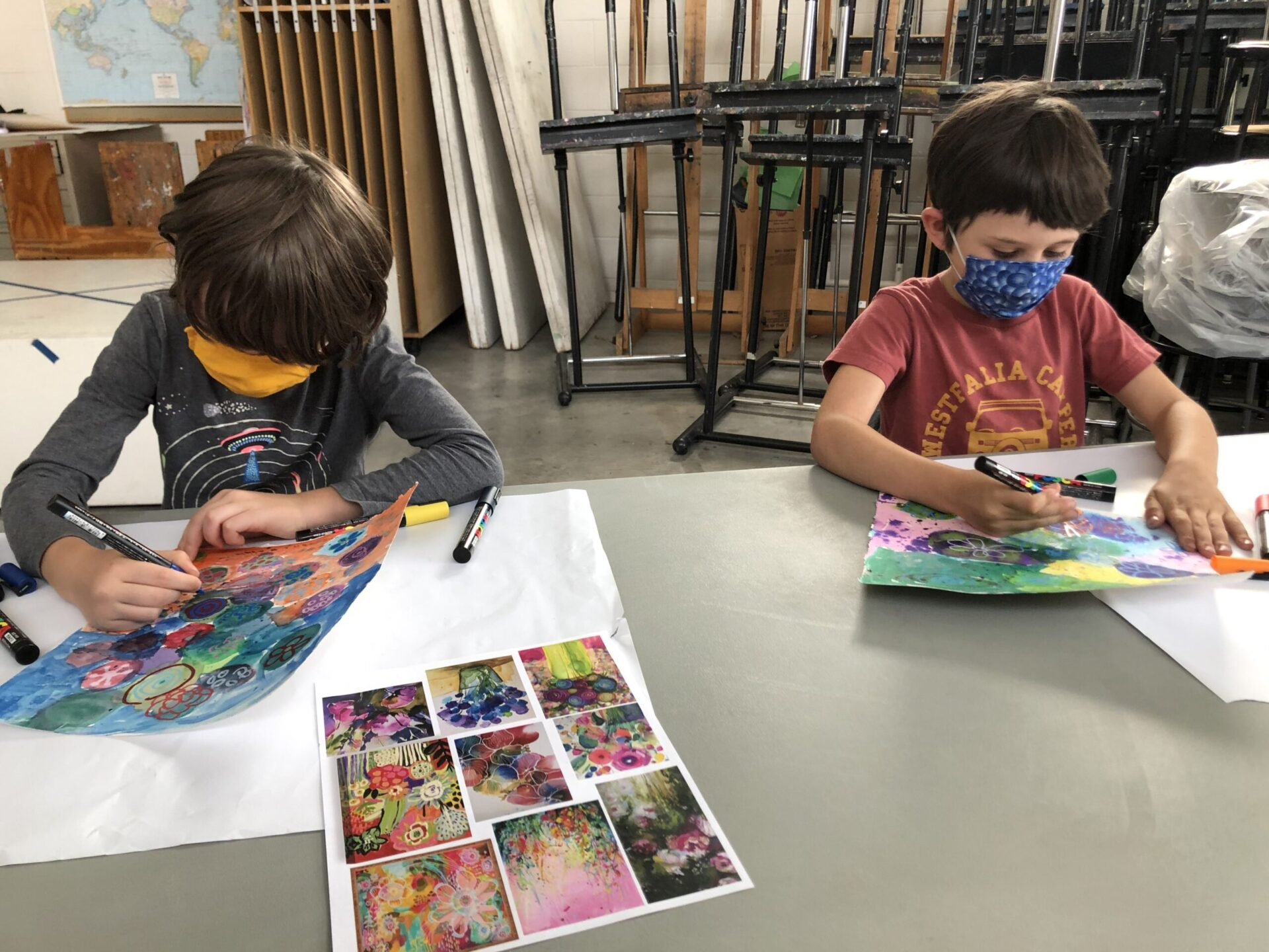 Two children color flowers with a marker.
