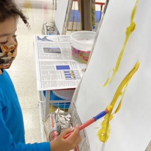 A child paints at an easel.