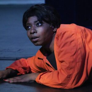 An actor lies on the stage floor